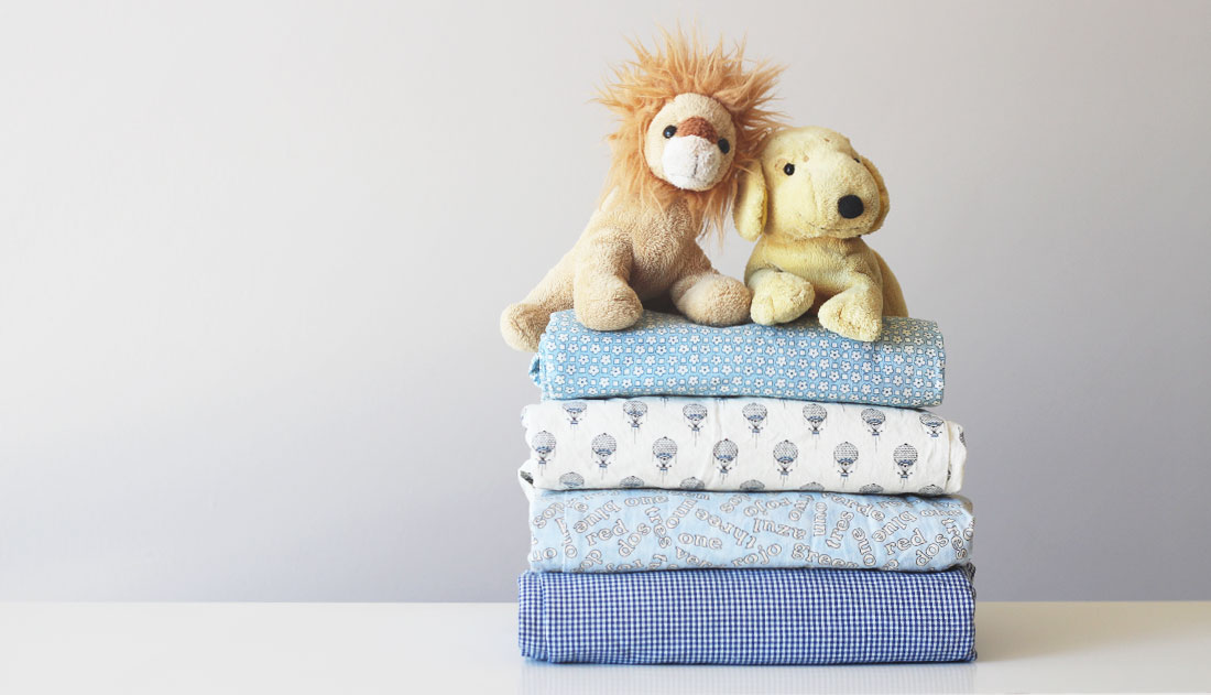 Simba and Spot toys on stack of folded pants.