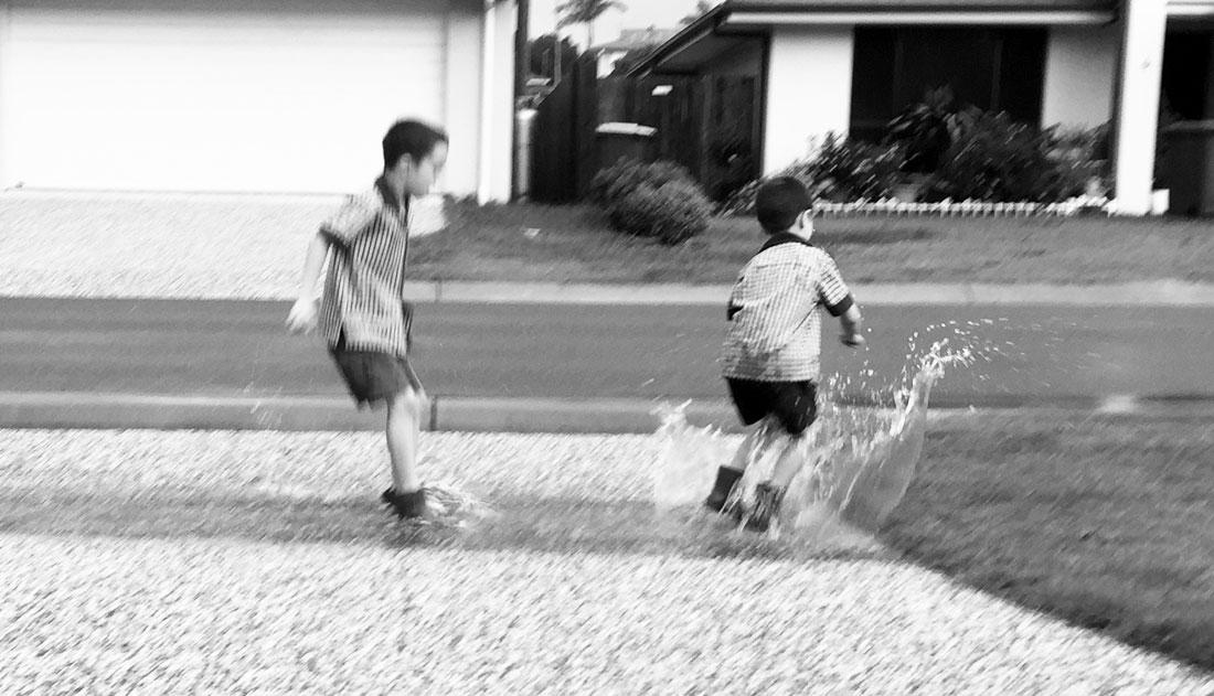 boys splashing in puddle