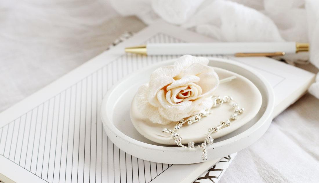 rose hair pin and bracelet on ceramic plate