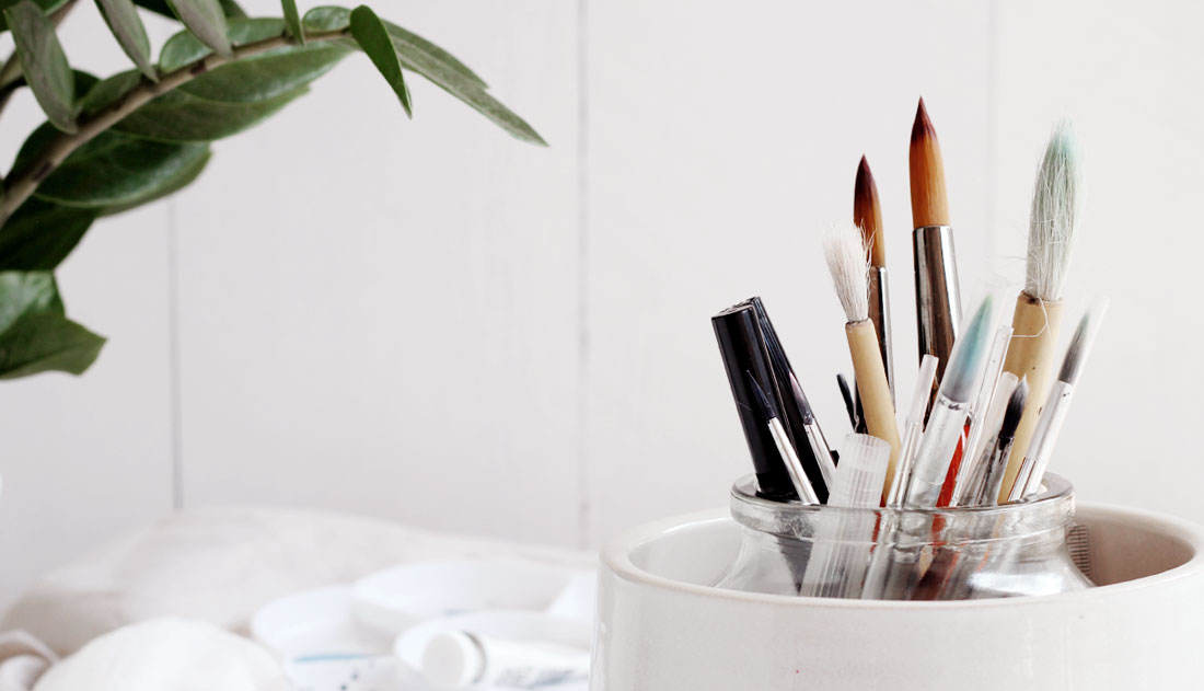 paintbrushes in white pot