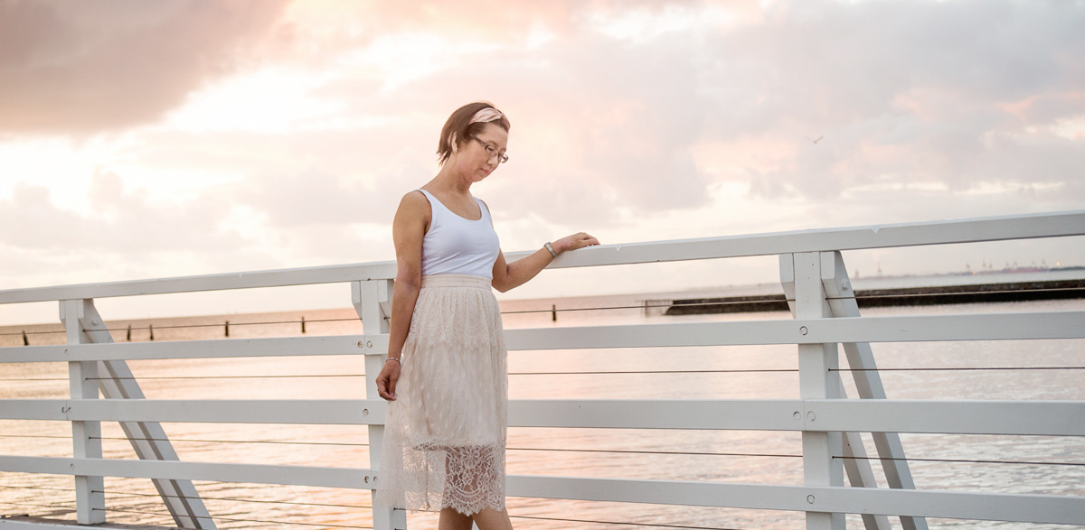 Woman standing on a pier at sunrise